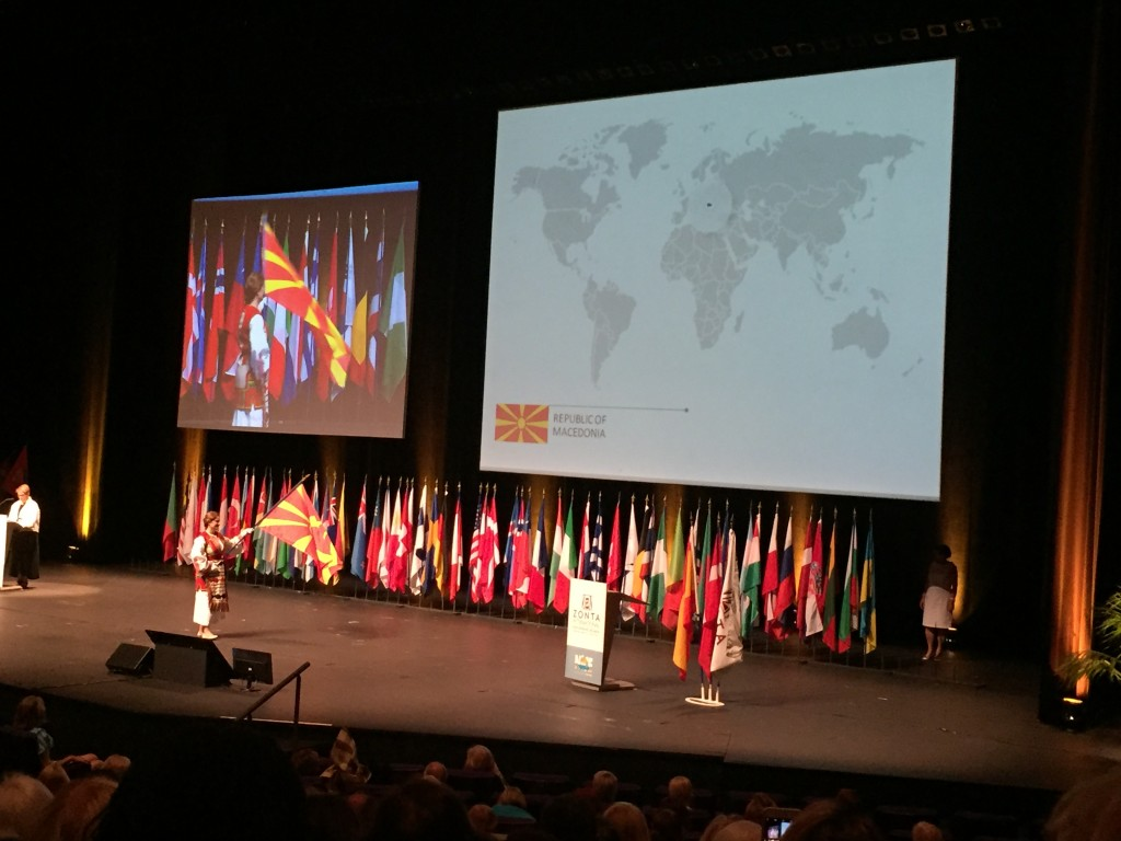 "This photo is from the flag ceremony that recognized all the countries where Zonta is active. There are currently 67 countries and there was a flag for each country, which was brought out while the country's national anthem was played. A map of the world was projected on the screen above the flags, and when each flag was brought out, the country was highlighted on the map so everyone could see where the country was located. Attendees described the ceremony as ""magical"" and ""very moving."""